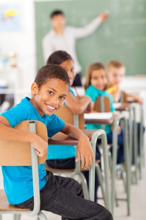 21290910 – smiling elementary school boy in classroom looking back