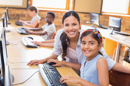 38078035 – cute pupils in computer class with teacher at the elementary school