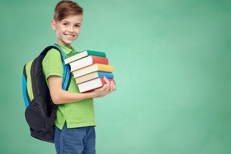 51808954 - childhood, school, education and people concept - happy smiling student boy with school bag and books over green school chalk board background